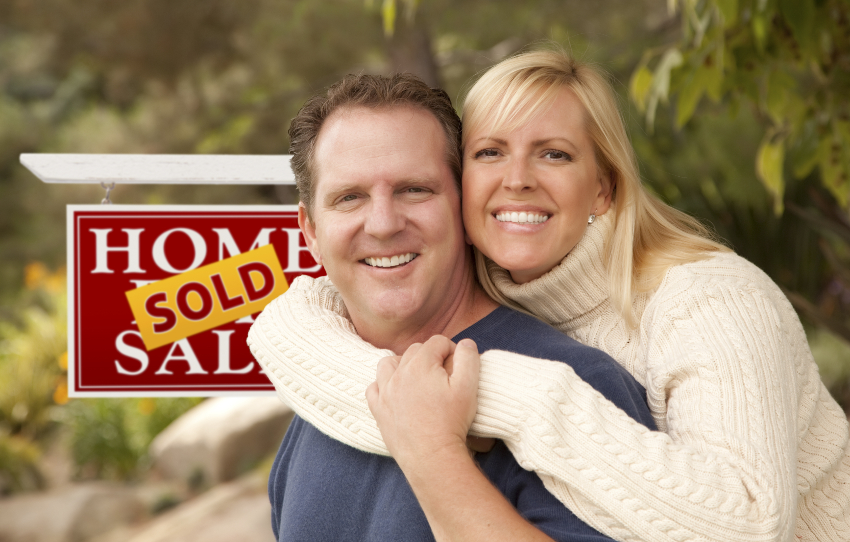 Happy Attractive Caucasian Couple in Front of Sold Real Estate Sign.